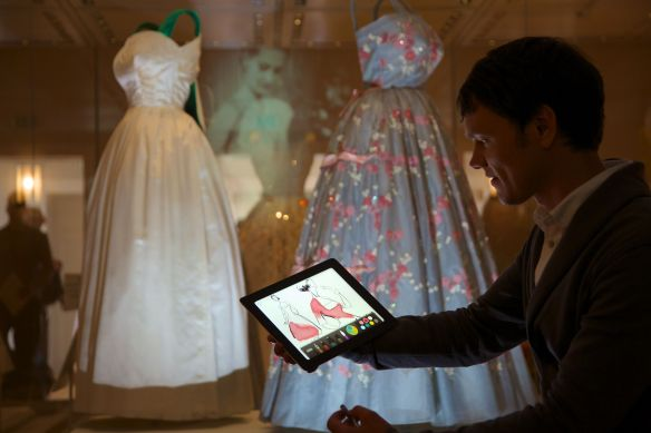 A visitor creates a fashion illustration using an interactive app with dresses worn by HM The Queen in the background.